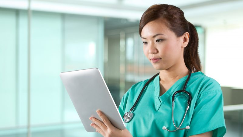 Female Asian doctor looking at a digital tablet & wearing a green scrubs plus stethoscope.