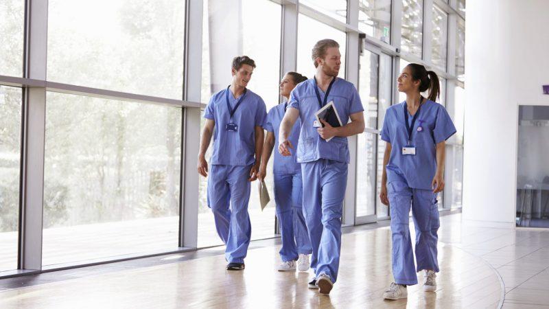 Four healthcare workers in scrubs walking in corridor